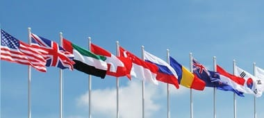 National flagpoles of different countries next to each other.